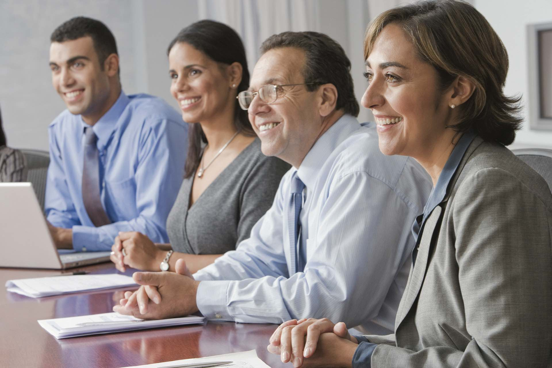 Group of business people at a conference table smiling with papers and a laptop on the Archangel Law Group website Business Law page
