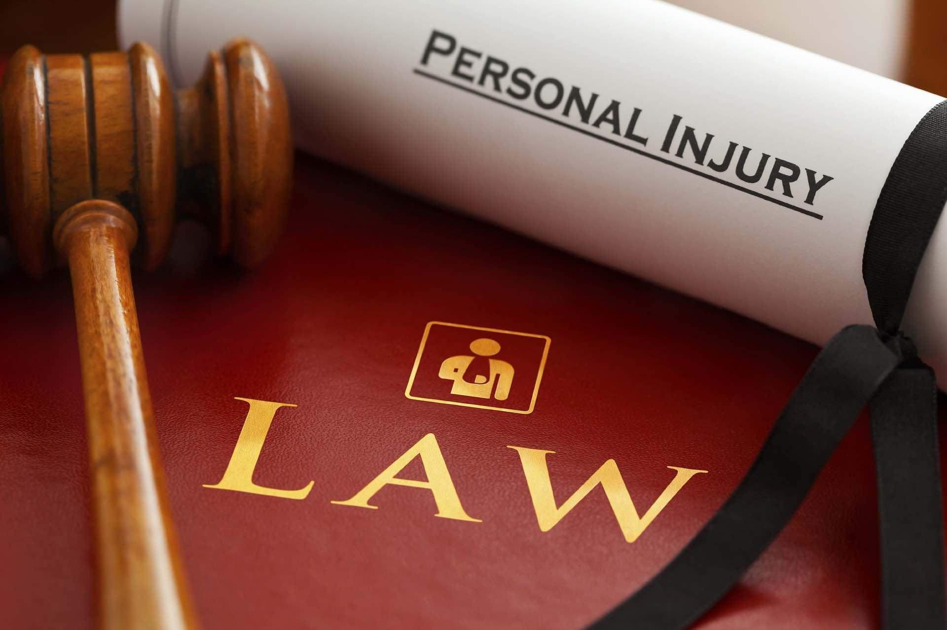 Law book with gold lettering with a wooden gavel and scroll with the words personal injury on the Archangel Law Group website Civil Litigation page