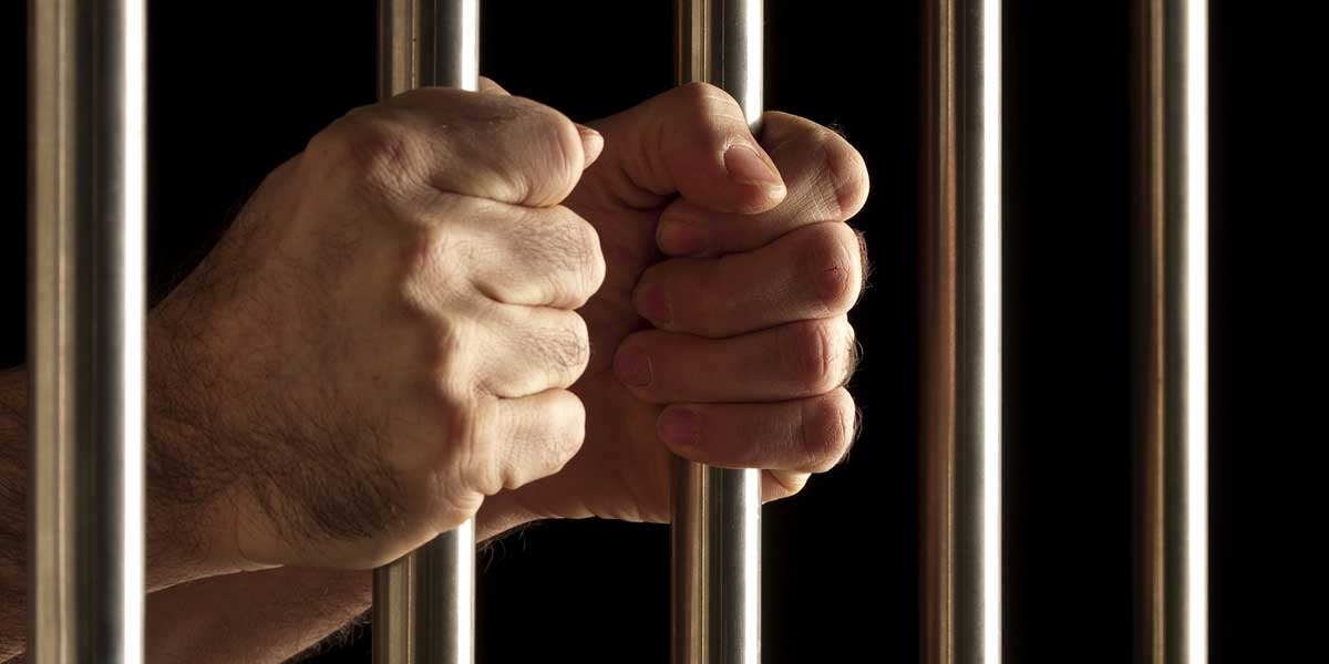 Hands holding onto the bars in a jail cell for Criminal Law on the Archangel Law Group website homepage