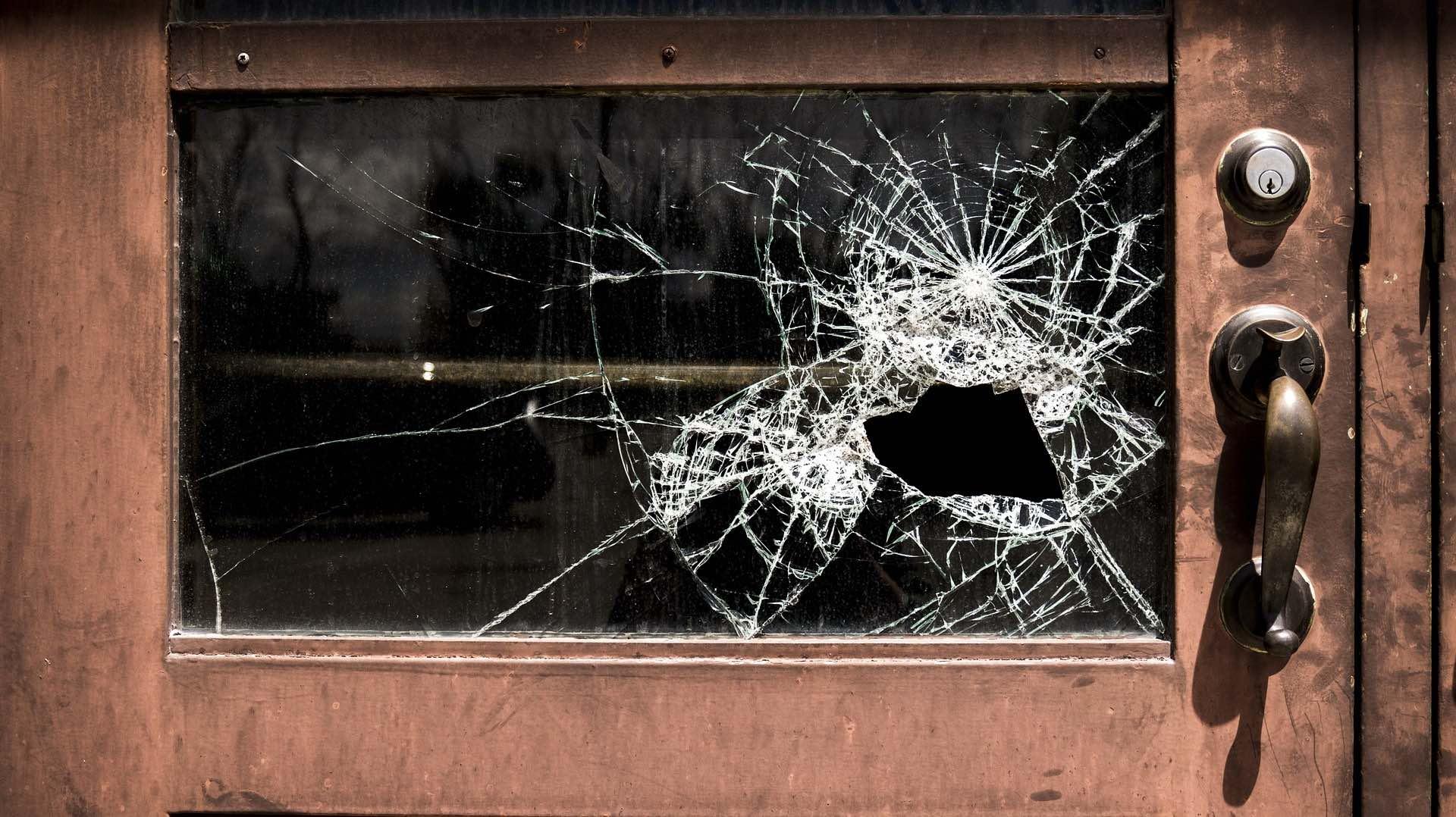 A broken window set in a brown wood door on the Archangel Law Group website Criminal Law page