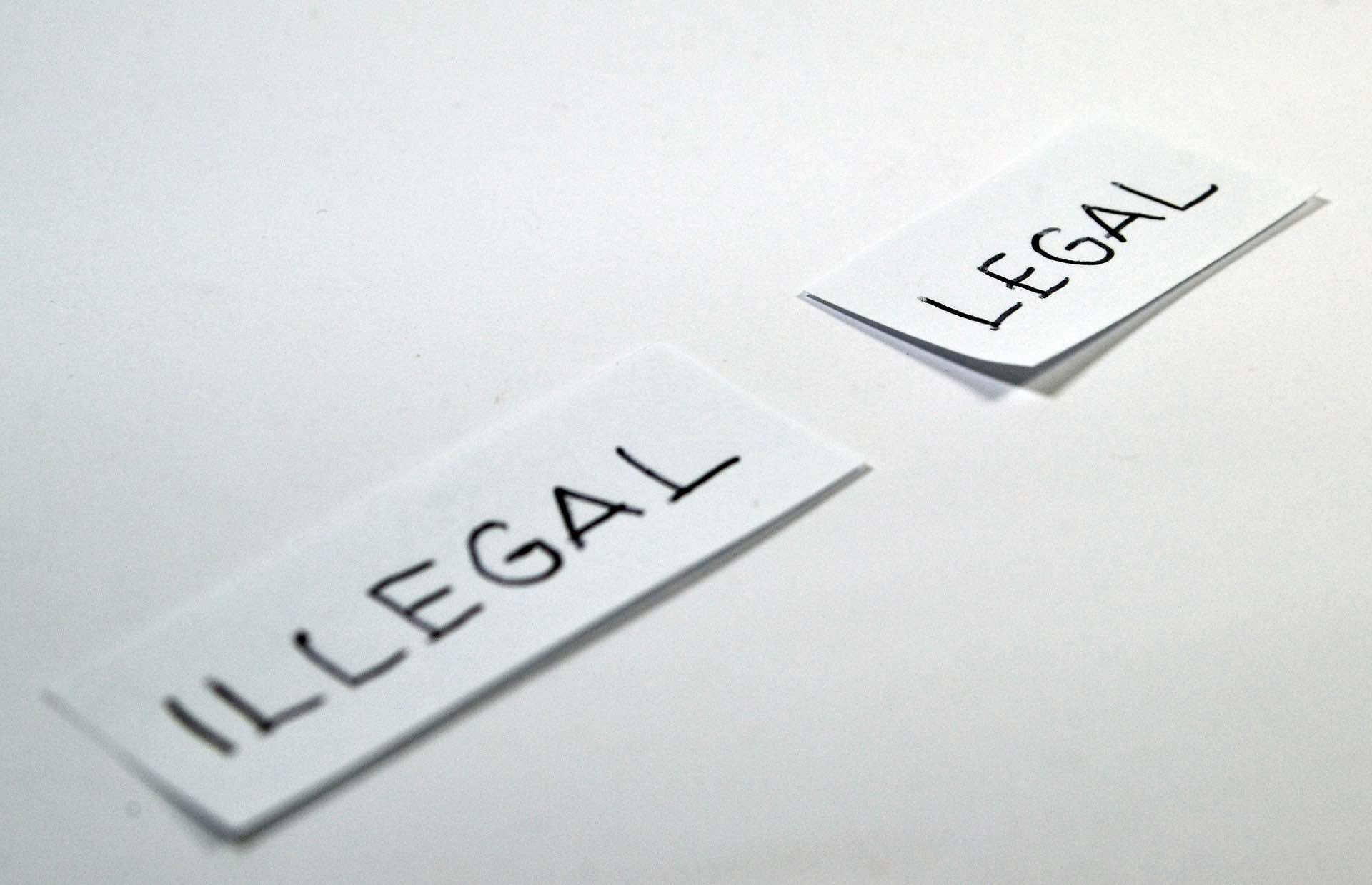 Two slips of white paper one with the word illegal and one with the word legal on the Archangel Law Group website Criminal Law page