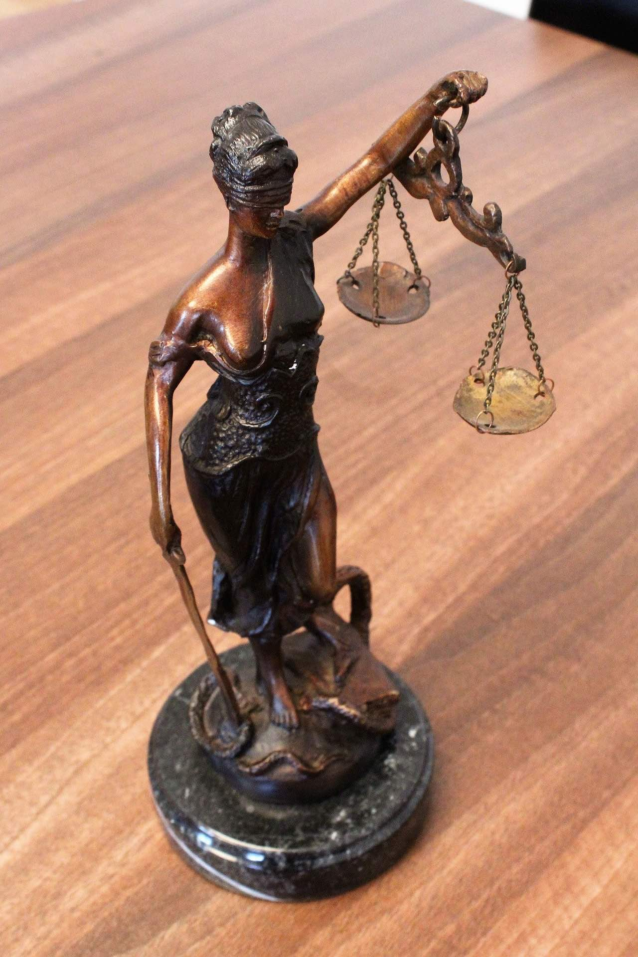 Lady Justice holding scales on a wooden table on the Archangel Law Group website homepage