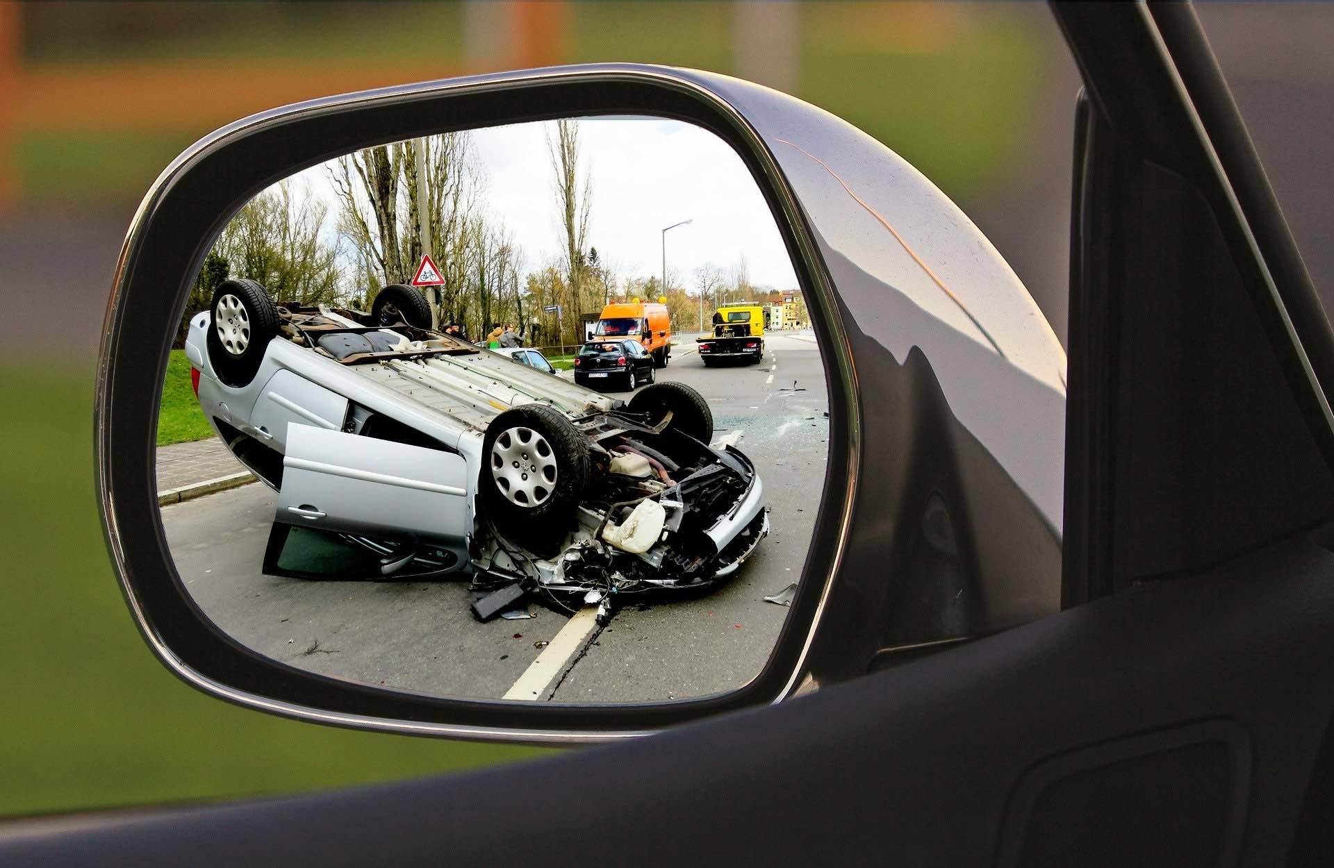 A traffic accident with a white car flipped on its roof as seen through a side mirror on the Archangel Law Group website Traffic Court page