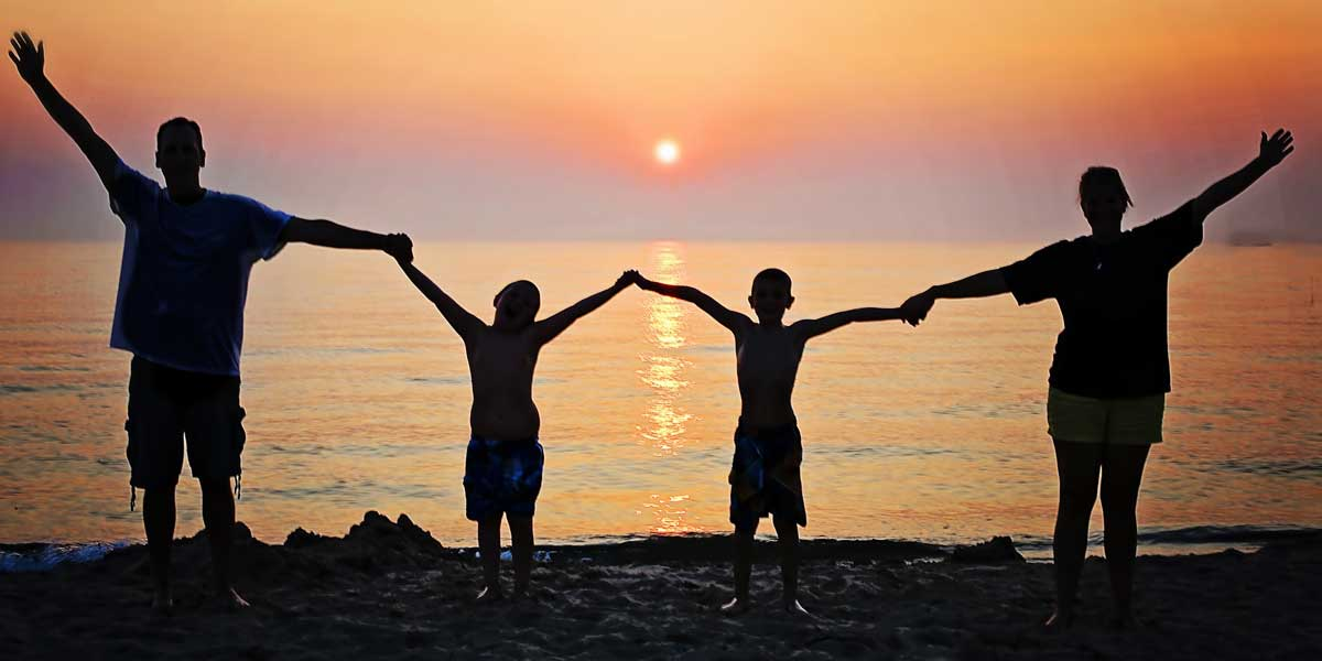 Silhouette of family holding out hands against the sun setting on the beach for Wills, Trusts & Estates on the Archangel Law Group website homepage