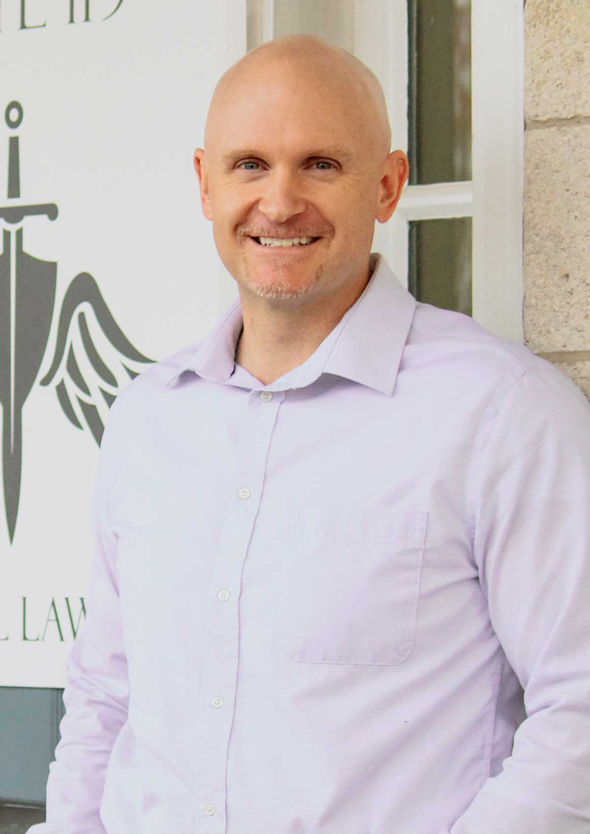 Christian Blank in a white dress shirt standing in front of the Archangel Law Group logo