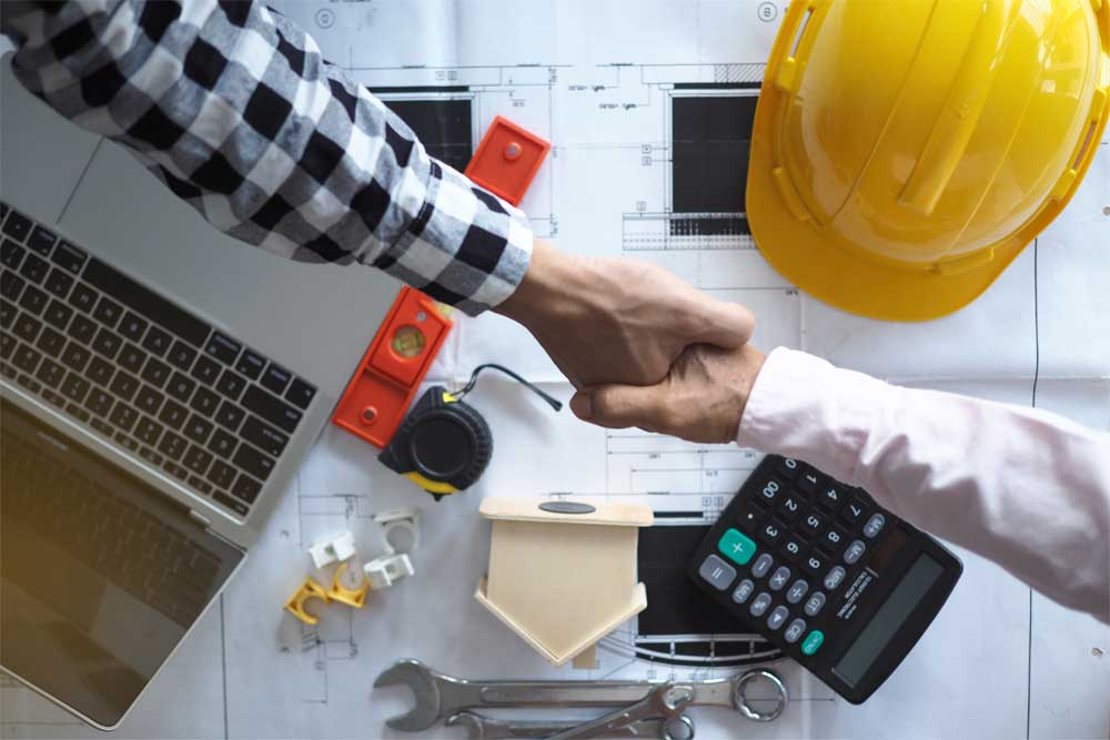 Two men shaking hands above construction related items
